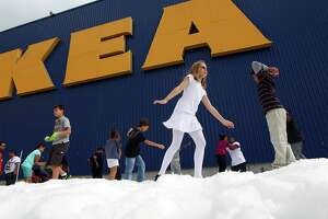 Children play in a mound of snow as IKEA Houston hosted a Swedish-inspired holiday experience complete with real snow, free breakfast, live reindeer and a visit from Jultomten, Sweden's Santa Claus Friday, Nov. 23, 2012, in Houston.