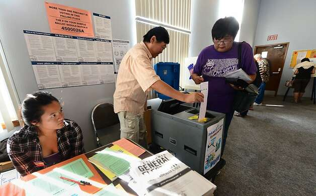 Election official Henry Tung (C) helps Kiyoko Nishi (R) drop her vote into the ballot box at a polling station at St. Paul's Lutheran Church in Monterey Park, Los Angeles County, on November 6, 2012 in California, as Americans flock to the polls nationwide to decide between President Barack Obama, his Rebuplican challenger Mitt Romney, and a wide range of other issues. Monterey Park is one of six cities in California's 49th Assembly District, the state's first legislative district where Asian-Americans make up the majority of the population.    AFP PHOTO/Frederic J. BROWNFREDERIC J. BROWN/AFP/Getty Images Photo: Frederic J. Brown, AFP/Getty Images
