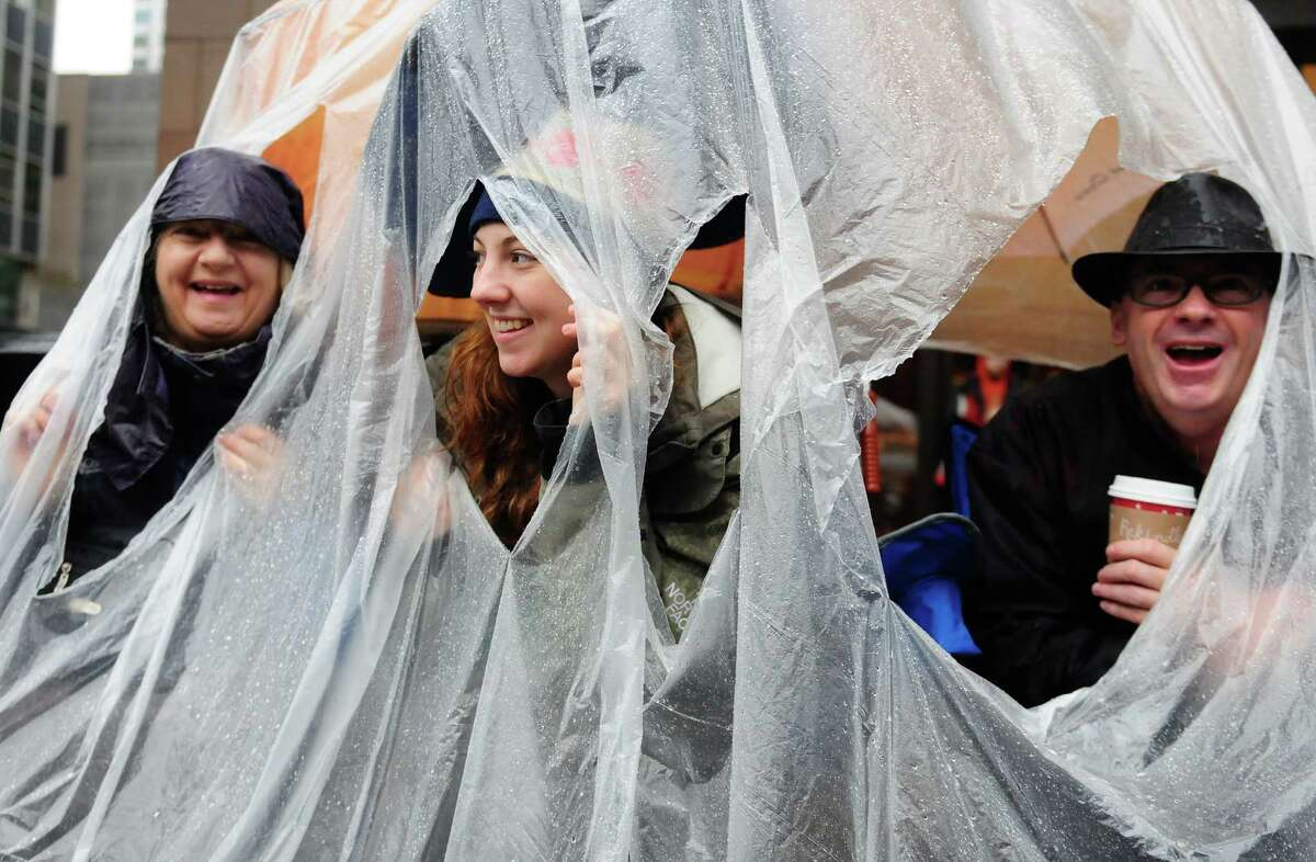 From left: Molly, Holly and Dave Hancock of Mercer Island smile as they look out at the parade from the dry comfort of their DIY umbrella tarp.