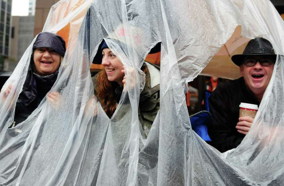 From left: Molly, Holly and Dave Hancock of Mercer Island smile as they look out at the parade from the dry comfort of their DIY umbrella tarp. Photo: LINDSEY WASSON / SEATTLEPI.COM