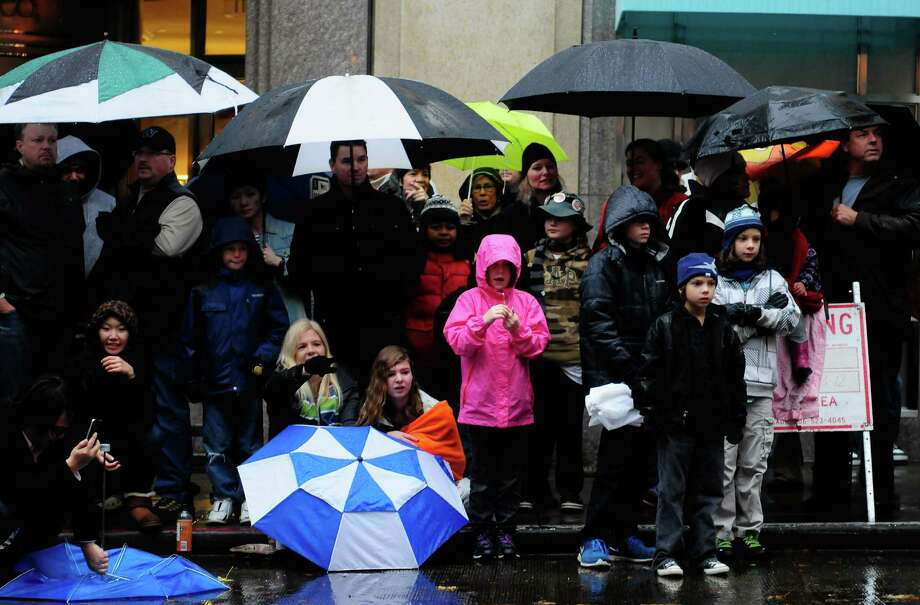 Spectators look on as a group of St. Bernards pass by during the Macy's Holiday Parade. Photo: LINDSEY WASSON / SEATTLEPI.COM