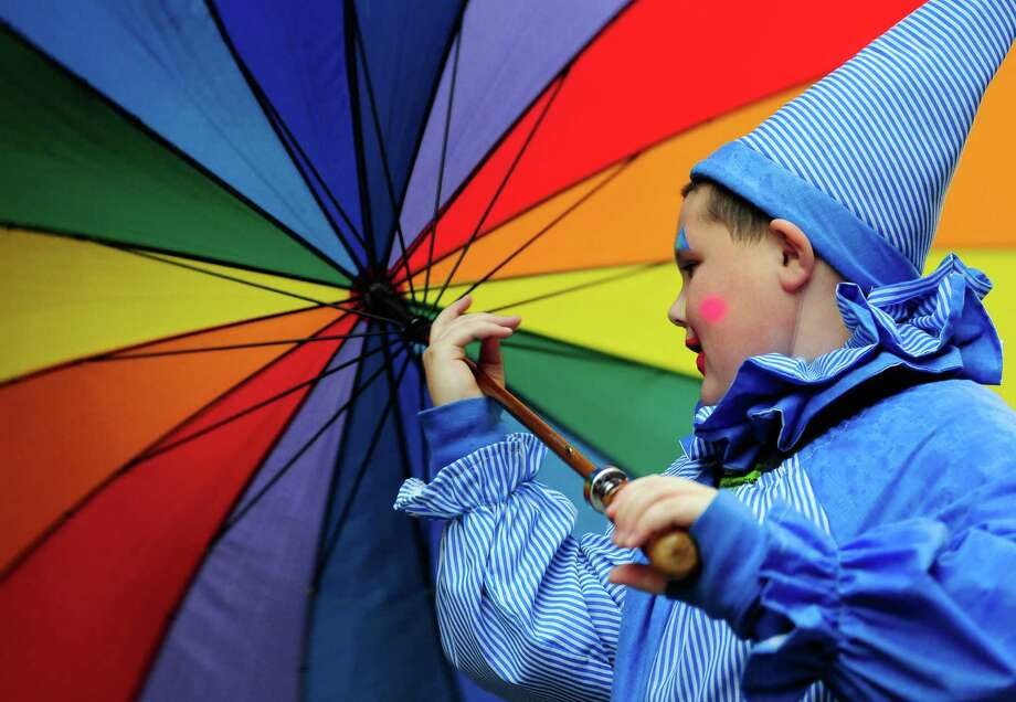 Dressed as a clown, 10-year-old Hunter Johnson twirls his umbrella as he waits to join the parade. Photo: LINDSEY WASSON / SEATTLEPI.COM
