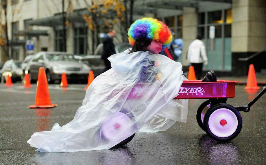 Donovan Colby-Sanchez, 22 months,  wears a poncho to ward off the rain as he rides in a wagon. Photo: LINDSEY WASSON / SEATTLEPI.COM