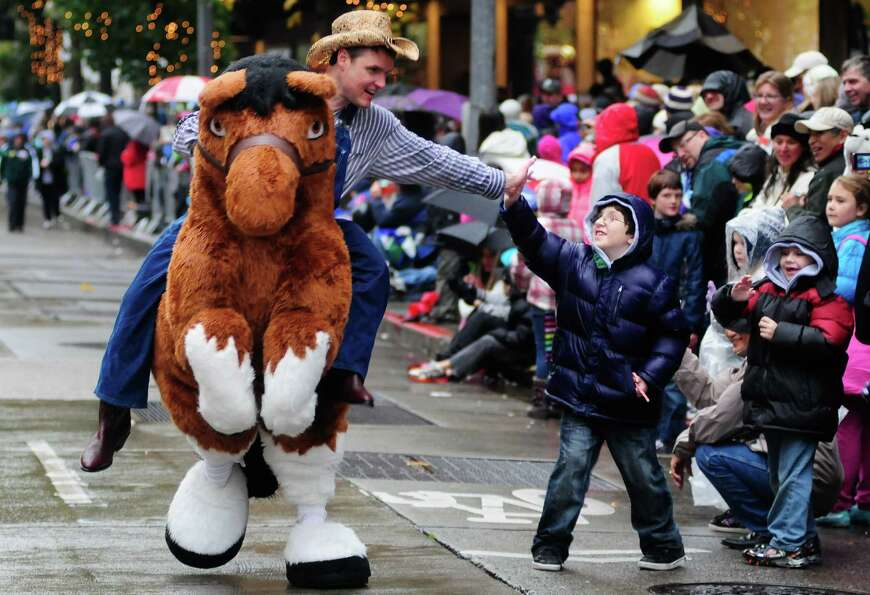 A man dressed as a cowboy gives a young boy a high-five as he