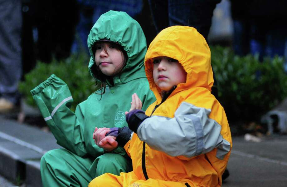 Ryan Marie Aijen, 7, and Oliver Aiken, 3, hold hands as they wave at parade participants. Photo: LINDSEY WASSON / SEATTLEPI.COM