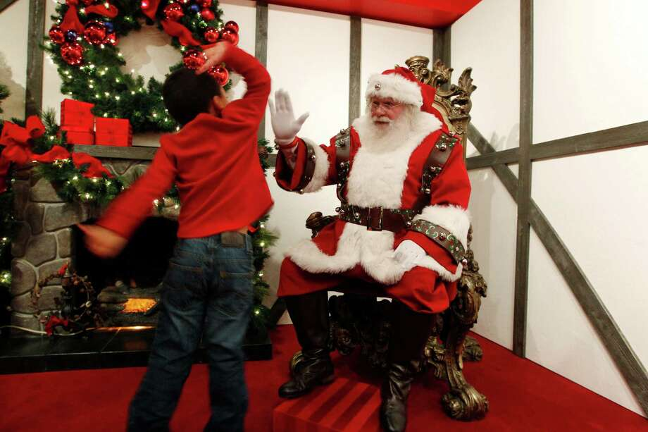 Jamir Ray, 4, of Astoria, Ore., races toward Santa and leaps to give him a high-five at a Macy's department store Friday, Nov. 23, 2012, in Seattle. Jamir was the first child in line for the first day of Santa appearances at the store. Photo: Elaine Thompson / Associated Press