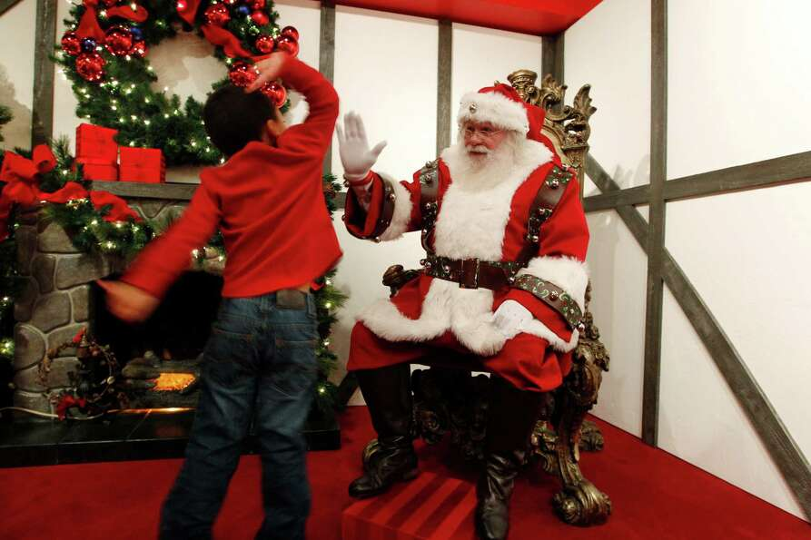 Jamir Ray, 4, of Astoria, Ore., races toward Santa and leaps to give him a high-five at a Macy's dep