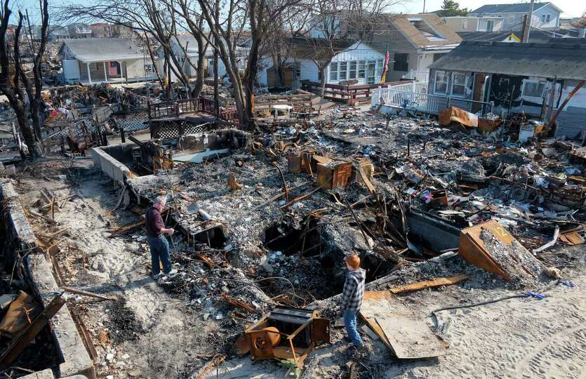 John Hardy, left, and his son, Liam, 13, visit the charred remains of his wife's parents home in the
