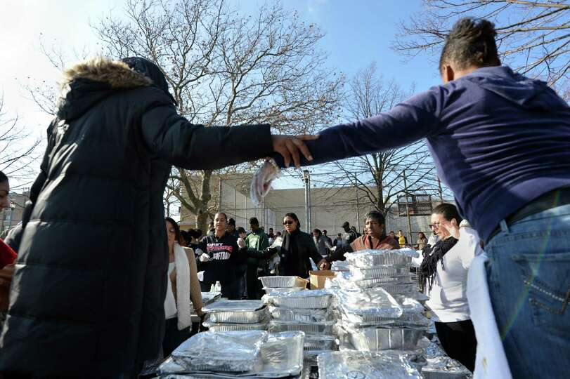 Volunteers say a prayer before serving Thanksgiving dinner to residents in the Rockaways section of