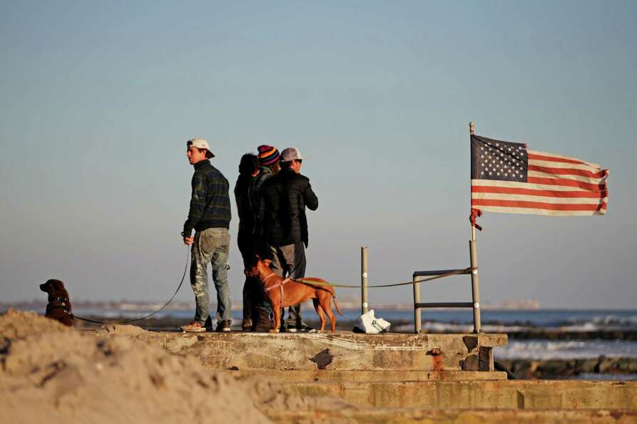 Residents of Rockaway Beach watch surfers while standing by a tattered flag on what is left of the b
