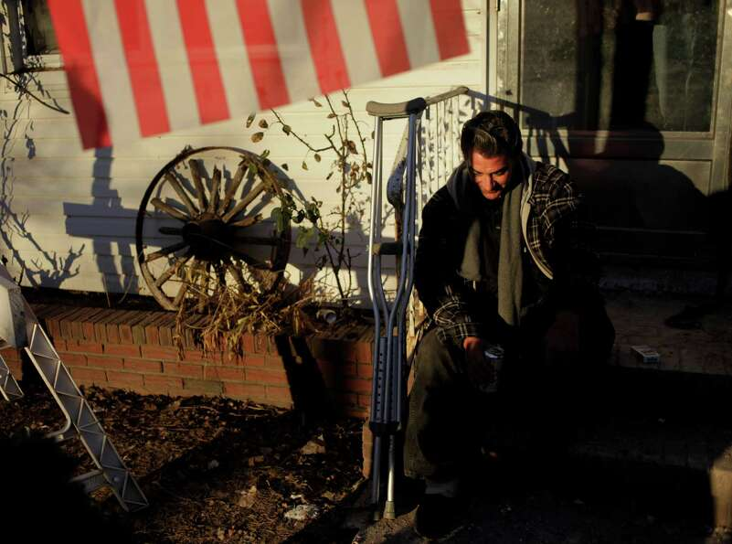 Ronny Kmiotek takes a break on his stoop while his house, which was damaged by Superstorm Sandy, is