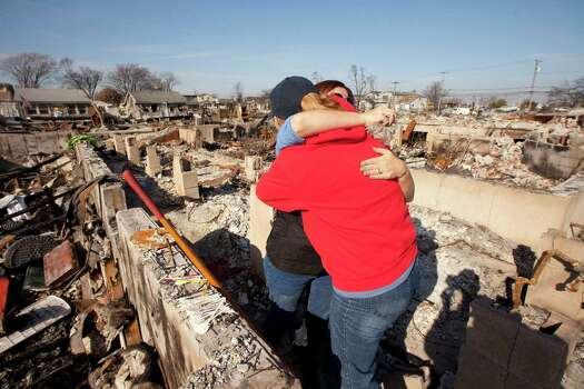 Deirdre Mathis McGovern, facing camera, gets a hug from a neighbor Friday, Nov. 23, 2012 as they meet up for the first time since Superstorm Sandy swept through the Breezy Point section of the Queens borough of New York. The fire destroyed more than 100 homes in the oceanfront community during the storm. Photo: Mark Lennihan, Associated Press / AP