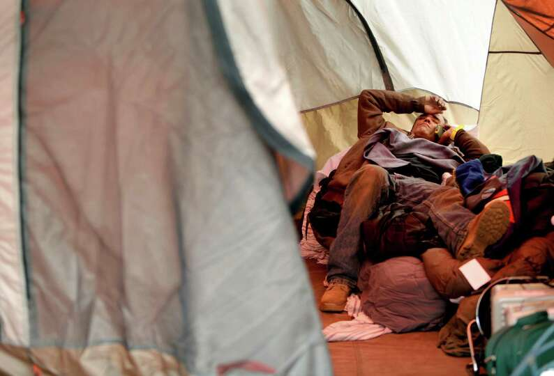 Anthony Gatti makes a call while resting the in a tent where he is living in the Midland Beach secti