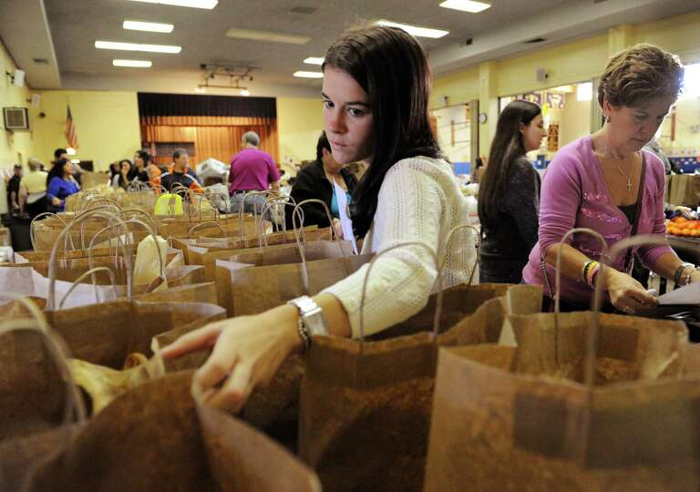 Michelle Devlin, center, checks the address on a bag containing a turkey dinner while her mother, Re