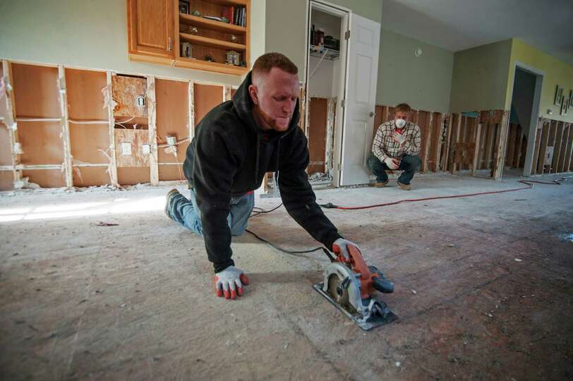 Sean Dickinson, left, cuts out a test patch of the sub-floor from Steve Engkilterra's house in Seasi
