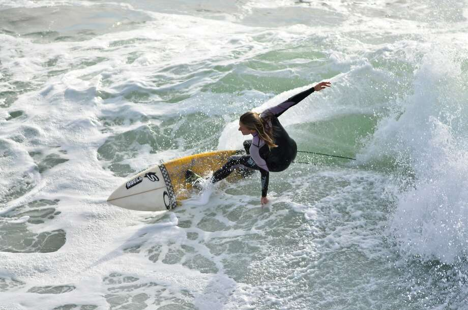 Savannah Shaughnessy catchs a wave at Steamer Lane near the Mark Abbot Memorial Lighthouse in Santa Cruz, Calif., on Monday, Nov. 19th, 2012. Photo: Thomas Webb, The Chronicle