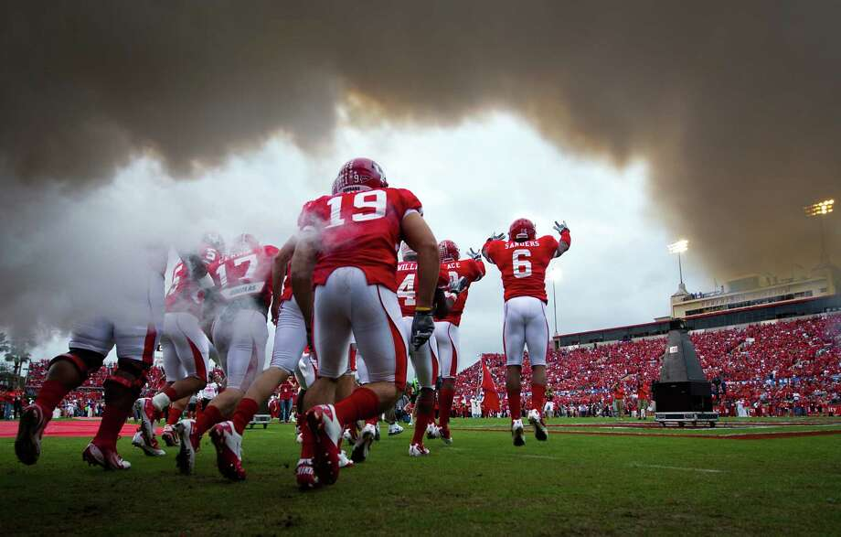 Houston players run onto the field through a cloud of smoke last year before playing SMU at Robertson Stadium, which hosts its last game Saturday. Photo: Smiley N. Pool, Staff / © 2011  Houston Chronicle