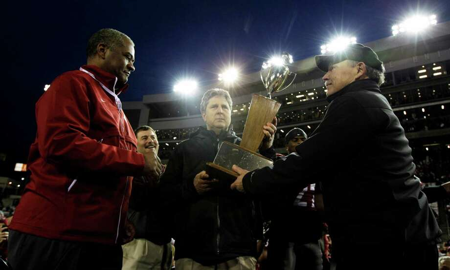 Washington State head coach Mike Leach, center, and Washington State president Elson Floyd, left, are presented with the Apple Cup trophy by Mike Gregoire, right, husband of Washington Gov. Chris Gregoire, after Washington State defeated Washington 31-28 in overtime. Photo: AP