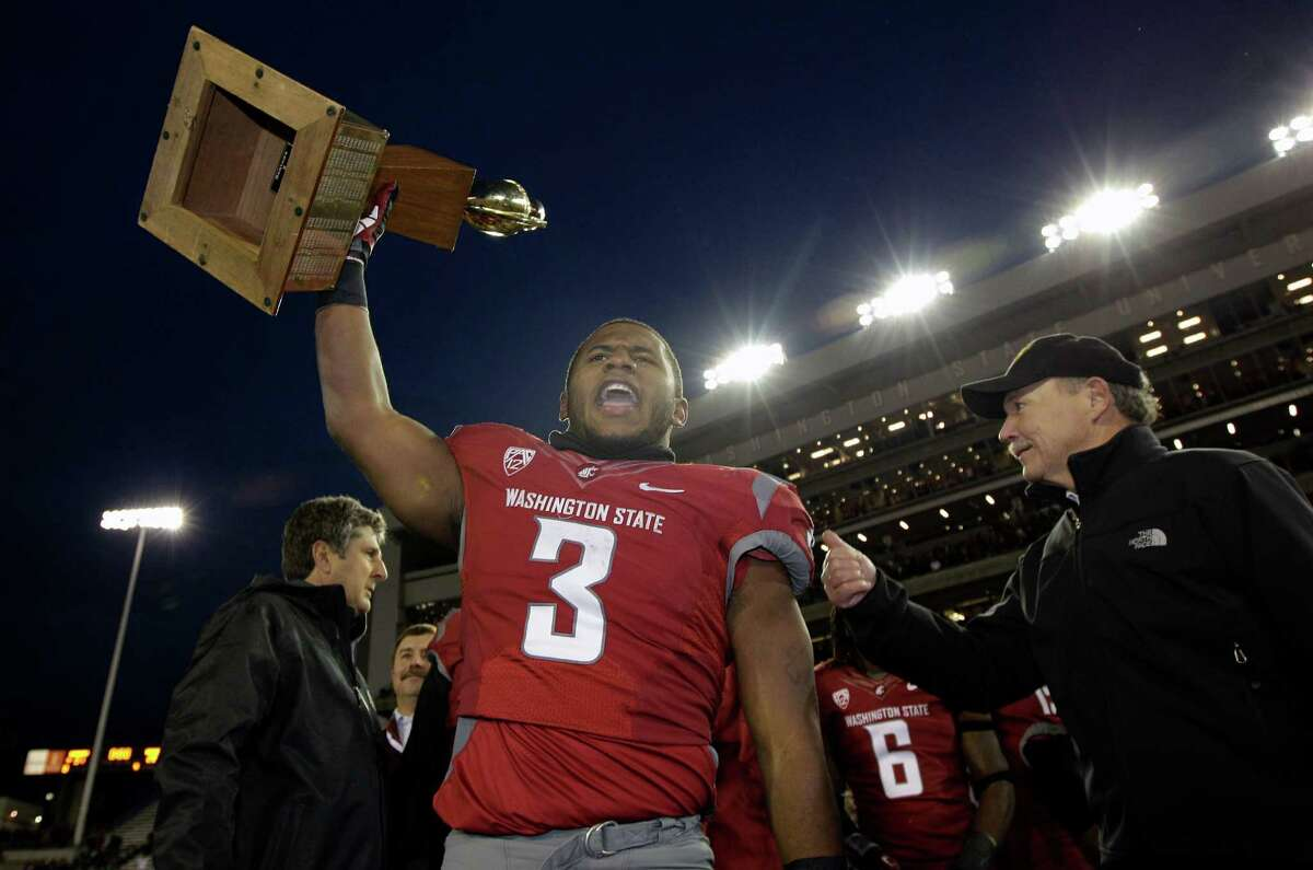 Washington State's Carl Winston (3) lifts the Apple Cup trophy as he celebrates after defeating Washington 31-28 in overtime in an NCAA college football game on Friday, Nov. 23, 2012, in Pullman, Wash. WSU head coach Mike Leach, left, and Mike Gregoire, right, husband of Washington Gov. Chris Gregoire, look on.