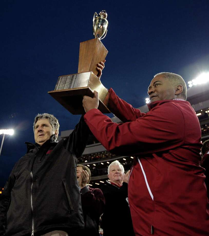 Washington State head coach Mike Leach, left, and Washington State president Elson Floyd, right, lift the Apple Cup trophy after defeating Washington 31-28 in overtime. Photo: AP