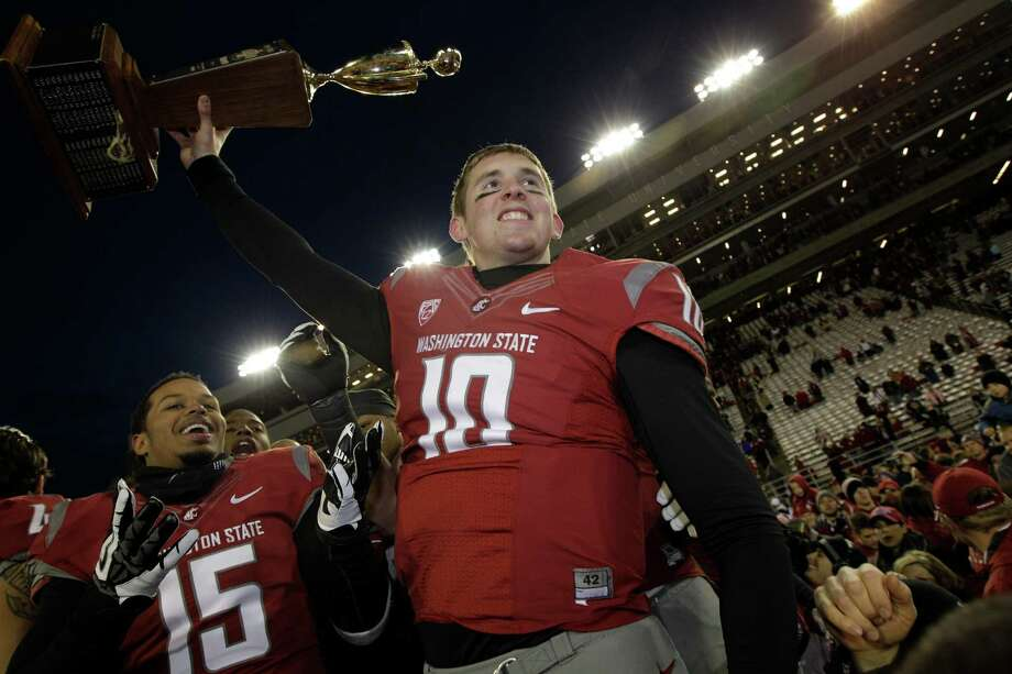 Washington State quarterback Jeff Tuel lifts the Apple Cup trophy as he celebrates with Tyree Toomer, left. Photo: AP