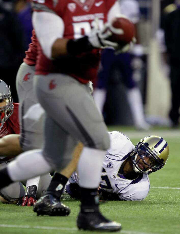 Washington quarterback Keith Price, lower right, looks on as Washington State's Kalafitoni Pole intercepts his pass on the first play of overtime. Photo: AP