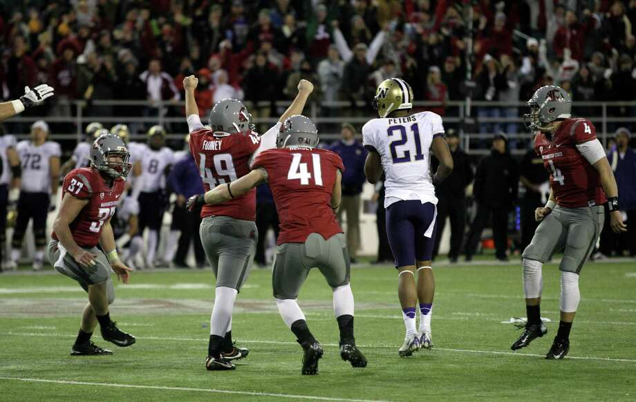Washington State's Max Hersey (41) and Jared Byers (37) move to celebrate with teammate Andrew Furney (49), as Washington's Marcus Peters (21) walks off the field after Furney kicked the game-winning field goal in overtime. WSU holder David Gilbertson (4), right, looks on. Photo: AP