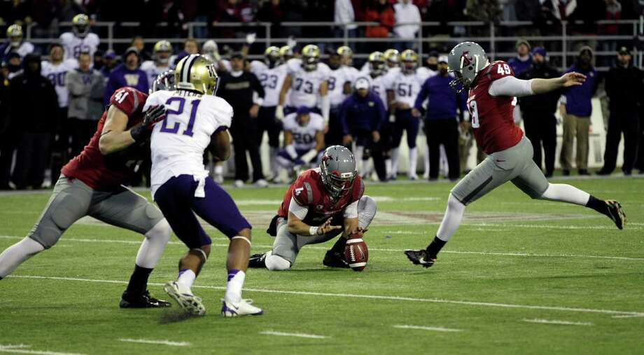Washington State's Andrew Furney, right, kicks the game-winning field goal in overtime against Washington. WSU's David Gilbertson (4) holds the ball. Photo: AP
