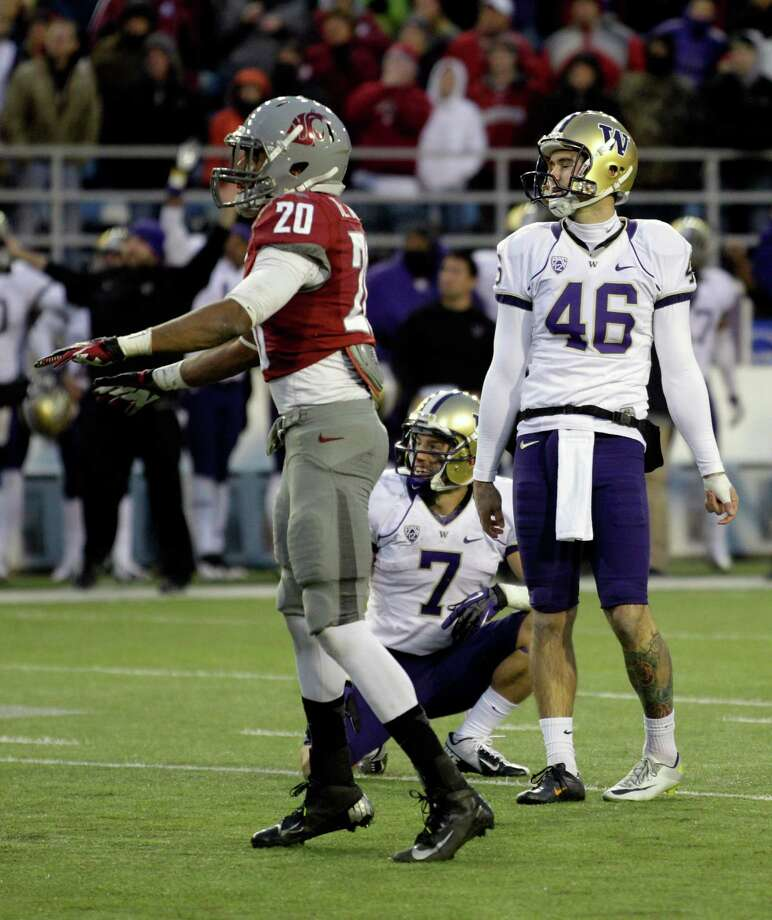 Washington kicker Travis Coons (46) reacts as Washington State's Deone Bucannon (20) signals that Coons missed a field goal at the end of regulation. Photo: AP