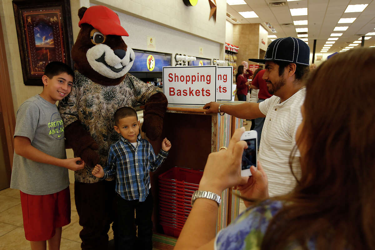 Jason Torres, left, and Angel Monroy strike a pose with the Buc-ee's Beaver mascot in Luling on Friday.