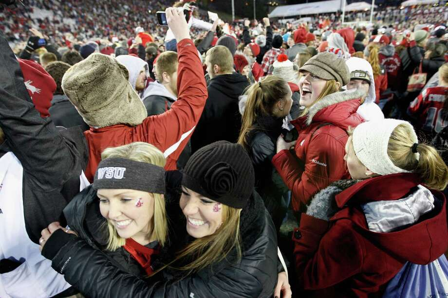 Fans rush the field as the Cougars win the Apple Cup 31-28 during overtime against the Washington Huskies. Photo: William Mancebo, Getty Images / 2012 Getty Images