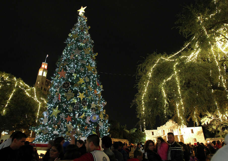 People gather at Alamo Plaza as the 10,000 colored LED lights on the 55-foot-tall white fir tree are illuminated for the holidays. Other trees in the area are draped in white lights. Photo: Kin Man Hui, San Antonio Express-News / ©2012 San Antonio Express-News