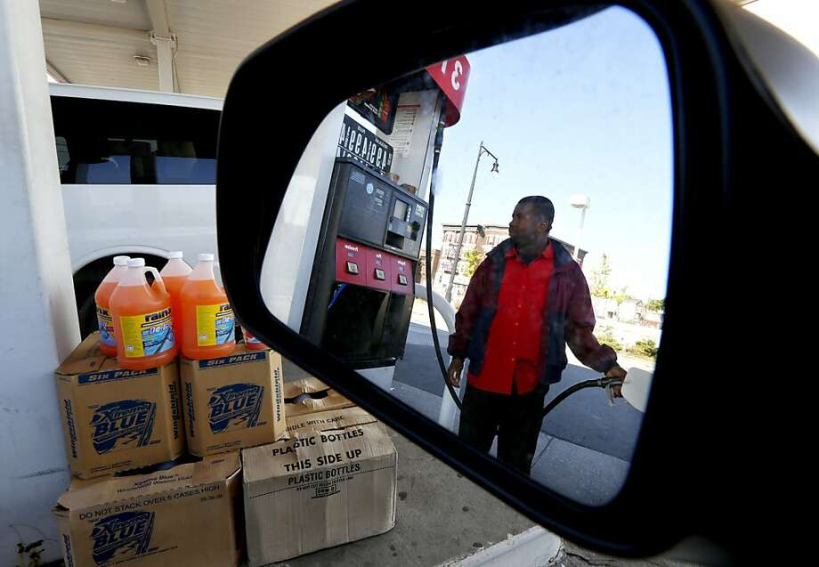 Youssouf Soukouna pumps gas in Newark, N.J.  Dropping gas prices are lifting drivers' spirits. Photo: Julio Cortez, Associated Press