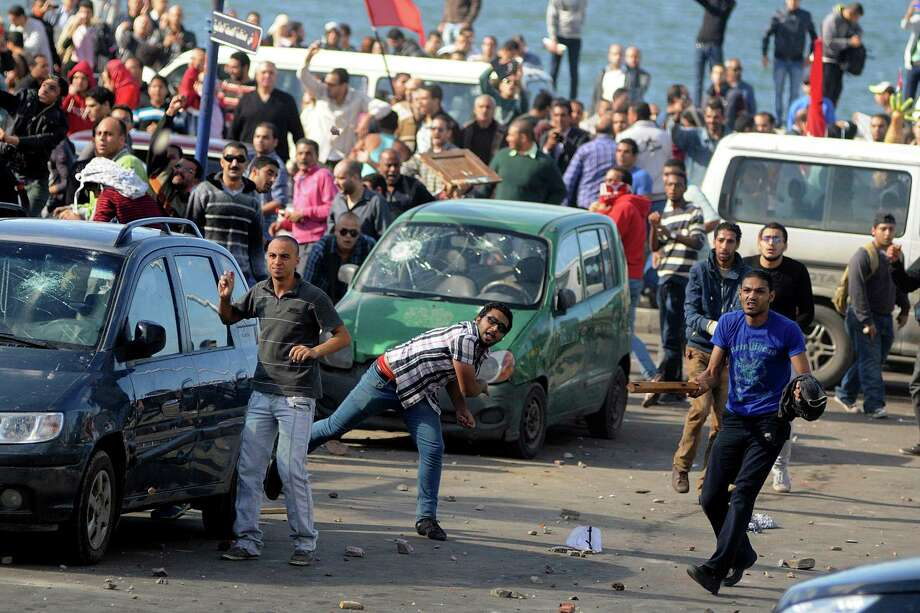 Protesters hurl stones during clashes between supporters and opponents of President Mohammed Morsi in Alexandria, Egypt, Friday, Nov. 23, 2012. Opponents and supporters of Mohammed Morsi clashed across Egypt on Friday, the day after the president granted himself sweeping new powers that critics fear can allow him to be a virtual dictator. Thousands from the two camps threw stones and chunks of marble at each other outside a mosque in the Mediterranean city of Alexandria after Friday Muslim prayers.  (AP Photo/Tarek Fawzy) Photo: Tarek Fawzy