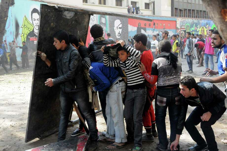 Egyptian protesters opposed to president Mohammed Morsi take cover during clashes with Morsi supporters near Tahrir Square in Cairo, Egypt, Friday, Nov. 23, 2012. Opponents and supporters of Mohammed Morsi clashed across Egypt on Friday, the day after the president granted himself sweeping new powers that critics fear can allow him to be a virtual dictator.(AP Photo/Mohammed Asad) Photo: Mohammed Asad
