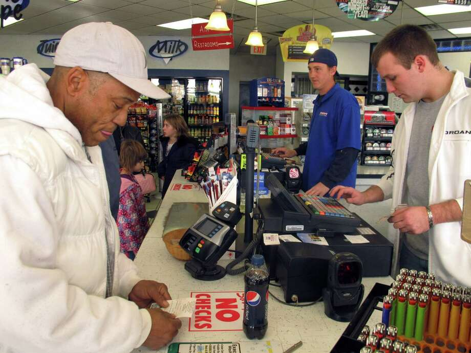 Michael Arrington, left, buys a Powerball ticket from cashier Lee Heilig, right, on Friday, Nov. 23, 2012, at a DeliMart convenience store in Iowa City, Iowa. The jackpot had reached $325 million as of Friday. (AP Photo/Grant Schulte) Photo: Grant Schulte