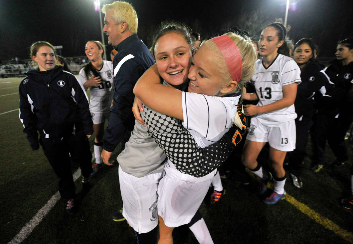 Goalie Ashley Houghton, left, hugs her teammate, Rachael Raffini, as the Immaculate High School girls soccer team celebrates its Class S state championship win over Portland at Municipal Stadium in Waterbury on Friday, Nov. 23, 2012. Immaculate won, 5-0.