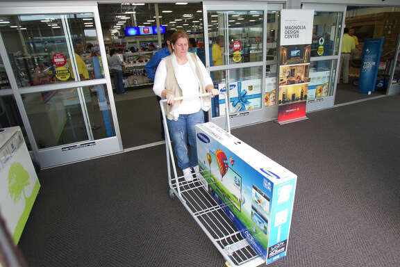 Barbara Coffey rolls a TV out of Best Buy during Black Friday, Nov. 23, 2012, in Houston. (Cody Duty / Houston Chronicle)