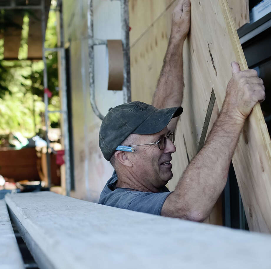 Mike Hartrich, president of Construction Guild US Inc. of Santa Cruz, Calif., installs new siding on a home in the Santa Cruz Mountains. His business connects trusted independent contractors with local customers. Photo: Contributed Photo, Virginia Becker / Stamford Advocate Contributed