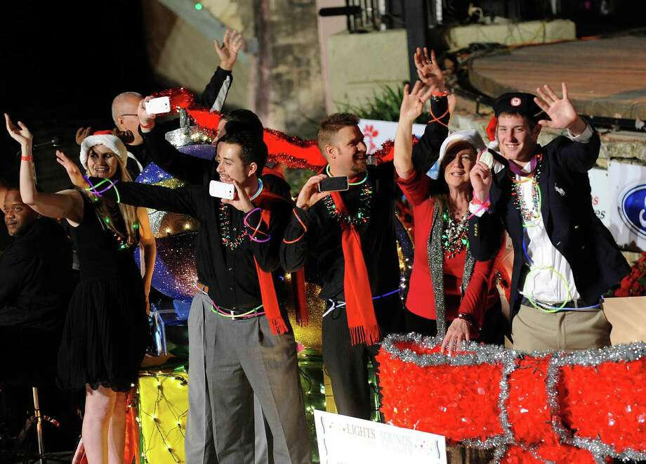 Grand Marshall Jimmy Feigen, right, who won a swimming Silver Medal at the 2012 Olympics, holds up his medal as he rides on a float during the during the 30th annual Ford Holiday River Parade & Lighting Ceremony on the River Walk in downtown San Antonio on Friday, Nov. 23, 2012. Photo: Billy Calzada, San Antonio Express-News / San Antonio Express-News