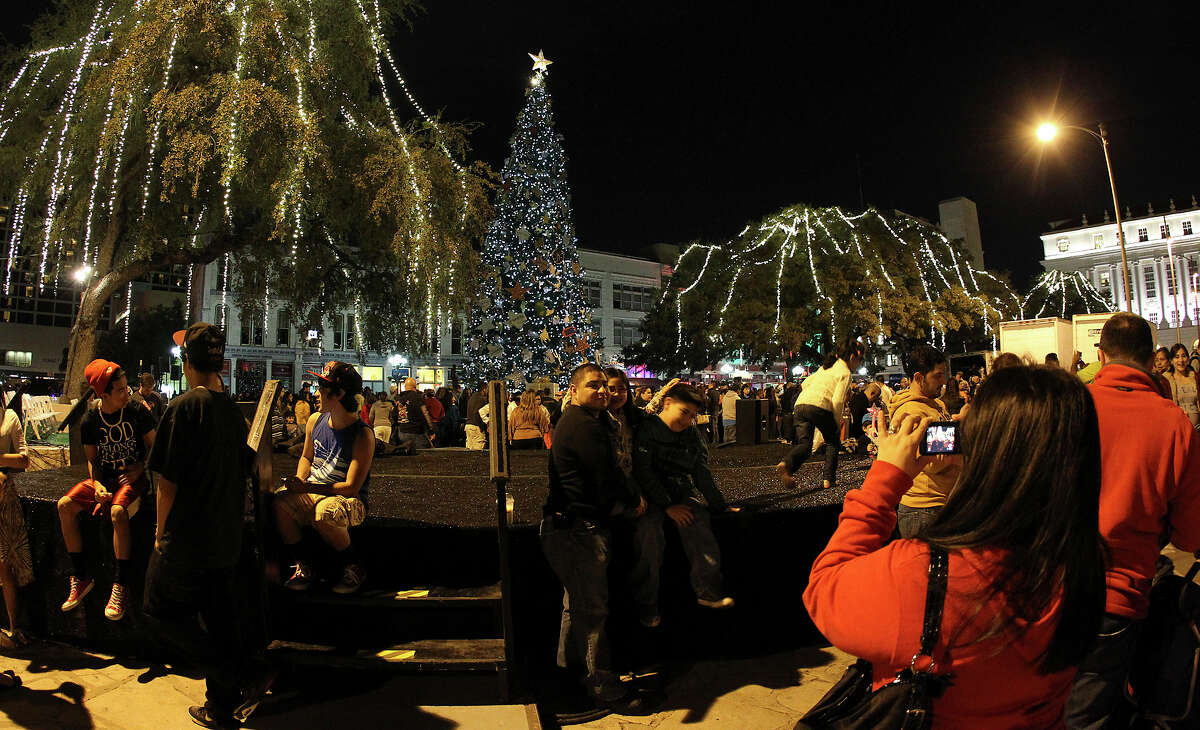 Families gather for photos at Alamo Plaza after the 28th Annual H-E-B Tree Lighting Ceremony on Friday, Nov. 23, 2012. The 55-foot tall fir tree was lit with 10,000 LED lights and with 450 ornaments. The event kicked off the holiday season followed by the 30th Annual Ford Holiday River Parade & Lighting Ceremony along the San Antonio River.
