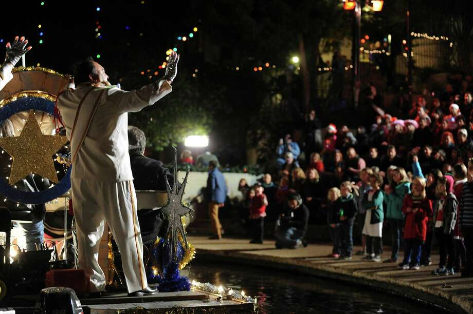 Rey Feo LXV aide minister Felix Trevino waves from atop a float during the 30th annual Ford Holiday River Parade  & Lighting Ceremony on the River Walk in downtown San Antonio on Friday, Nov. 23, 2012. Photo: Billy Calzada, San Antonio Express-News / SAN ANTONIO EXPRESS-NEWS