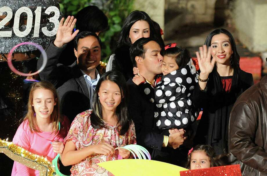 Congressional representative-elect Joaquín Castro, waving at left, and his twin brother, Mayor Julián Castro, who kisses his child, ride on a float during the 30th annual Ford Holiday River Parade  & Lighting Ceremony on the River Walk in downtown San Antonio on Friday, Nov. 23, 2012. Photo: Billy Calzada, San Antonio Express-News / SAN ANTONIO EXPRESS-NEWS