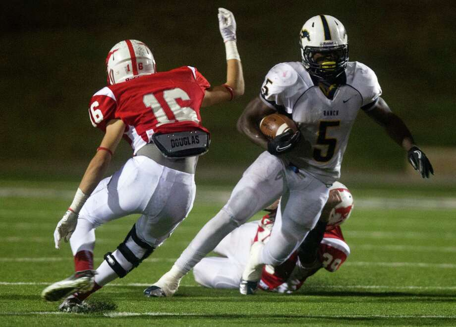 Cypress Ranch running back Keith Ford gets past Memorial defensive lineman Jack Berry (39) and defensive back Cameron Crawford (16) in the third quarter of the Class 5A Division II area round playoffs at Tully Stadium on Friday, Nov. 23, 2012, in Houston. Photo: J. Patric Schneider, For The Chronicle / © 2012 Houston Chronicle