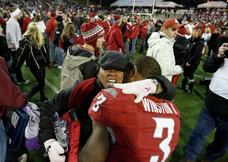 Carl Winston #3 of the Washington State Cougars celebrates with a friend on the field after the Cougars win the Apple Cup 31-28 during overtime against the Washington Huskies. Photo: William Mancebo, Getty Images / 2012 Getty Images