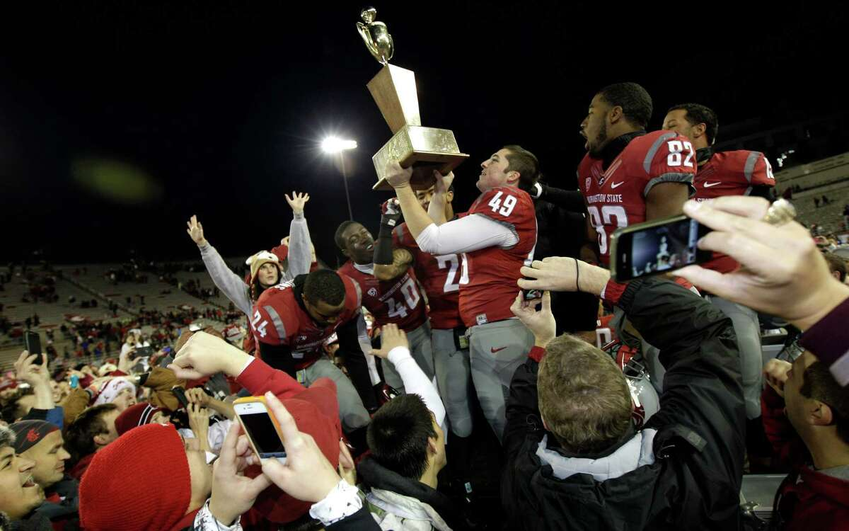 Washington State kicker Andrew Furney (49) holds the Apple Cup Trophy as he celebrates with teammates.