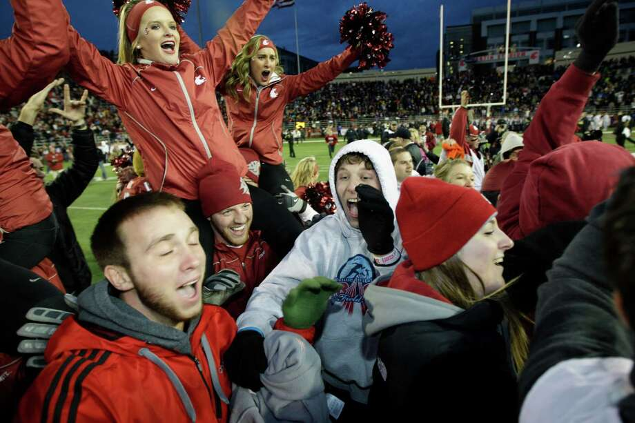 Fans  and cheerleaders celebrate on the field after Washington State defeated Washington 31-28 in overtime. Photo: AP