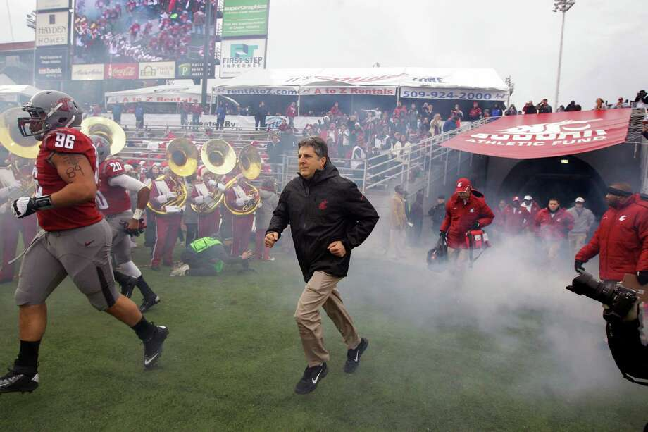 Washington State head coach Mike Leach, center, runs out of the tunnel with his team before the game. Photo: AP