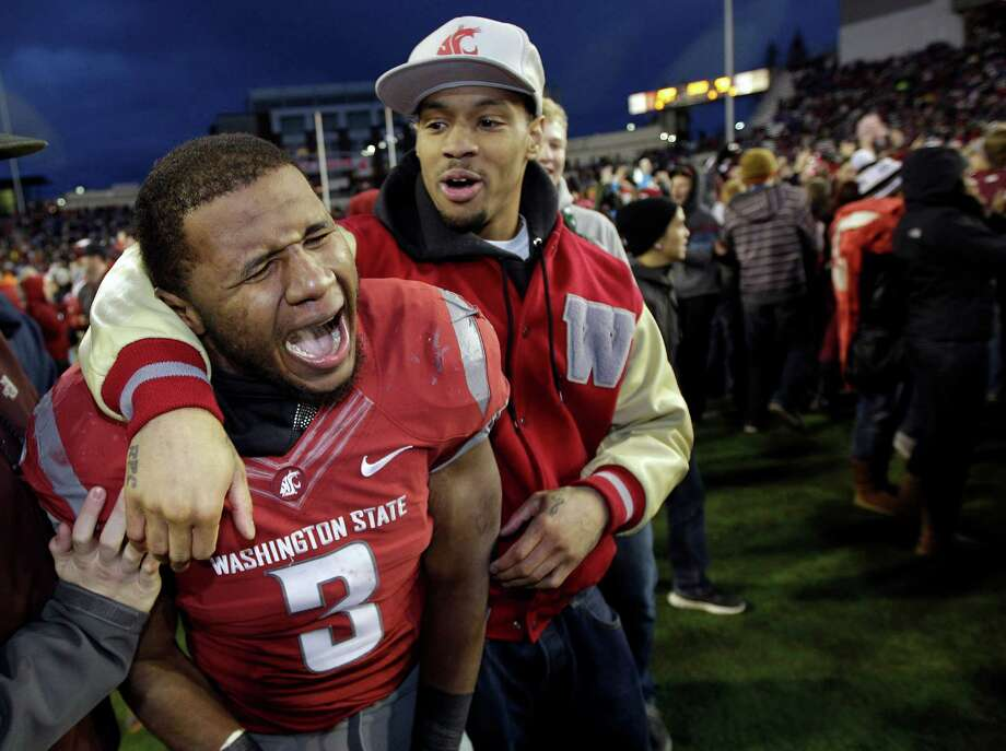 Washington State's Carl Winston (3) celebrates with a fan after Washington State defeated Washington in overtime. Winston had three touchdowns in the game. Photo: AP