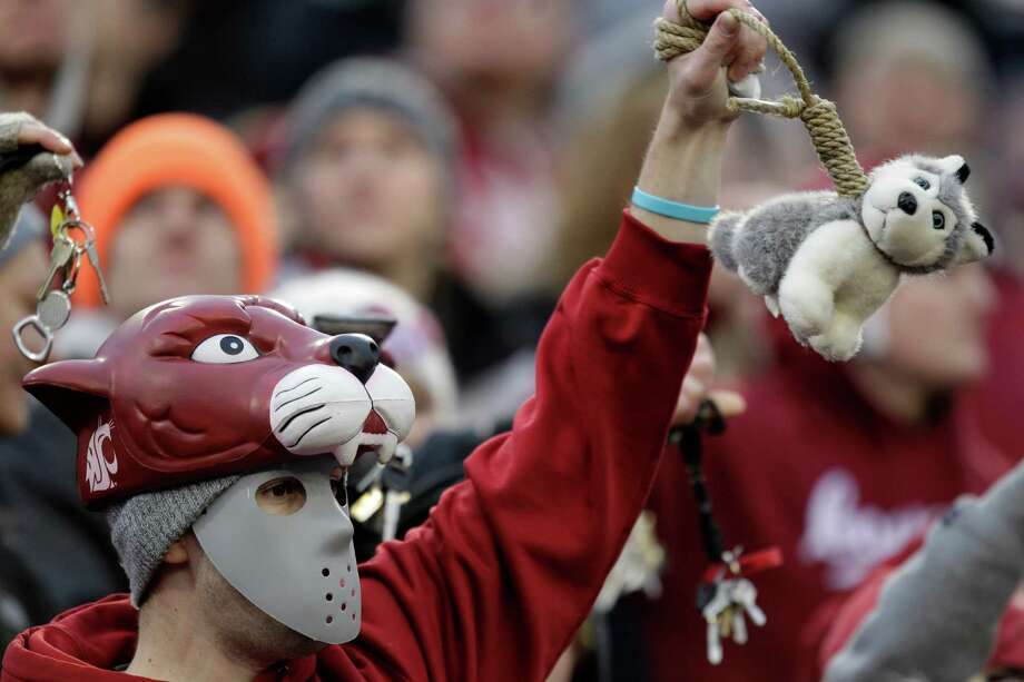 A Washington State fan holds a toy husky dog, the mascot of Washington, on a noose during the second half. Photo: AP